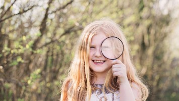 portrait of a cute young girl looking through magnifying glass at the park