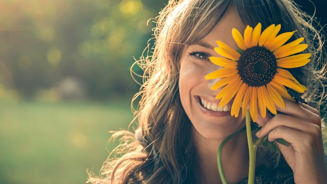 Girl in park covering face with sunflower